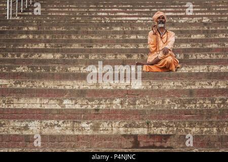 Unbekannter Mann Ruhe auf Schritte eines Ghat in Varanasi, Indien. Ghats ist ein Ort, wo die Menschen traditionell eine Ruhe und Meditation - Stockfoto