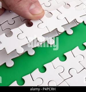 Die menschliche Hand ebnet den Weg an die Oberfläche des Puzzles, bilden einen grünen Raum. Das Konzept der Überwindung der Schwierigkeiten auf dem Weg zum succ - Stockfoto