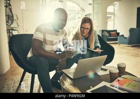 Zwei junge Designer arbeiten gemeinsam an einem Projekt mit einem Laptop während der Sitzung in einem stilvollen, modernen Büro - Stockfoto