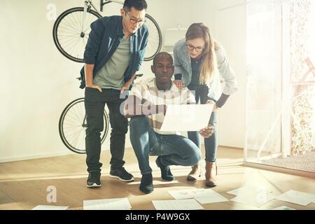 Vielfältige Gruppe von Arbeitskollegen lesen gemeinsam ein Dokument von Schreibarbeit, die Festlegung auf den Boden vor ihnen - Stockfoto