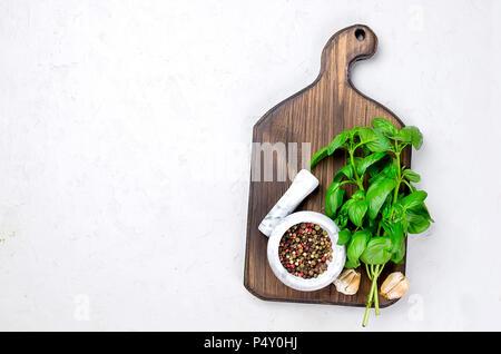 Brunch grüne Basilikum, Knoblauch, Salz und Gewürze auf einem leichten grauen Stein Hintergrund. Ansicht von oben, Kopieren. - Stockfoto