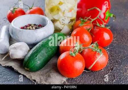 Marinierte würzigem Feta in einem Glas, Tomaten und Gurken für Salat. Auf einem dunklen Hintergrund. Kopieren Sie Platz für Ihren Text. - Stockfoto