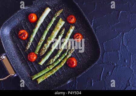 Gegrillter grüner Spargel und Tomaten cherry am Grill zubereitet Pan Am schwarzen Stein Hintergrund mit Platz für Text. Gesunde Ernährung Konzept. Ansicht von oben. Kopieren - Stockfoto