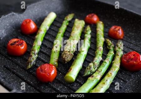 Gegrillter grüner Spargel und Tomaten cherry am Grill zubereitet Pan Am schwarzen Stein Hintergrund. Gesunde Ernährung Konzept. - Stockfoto