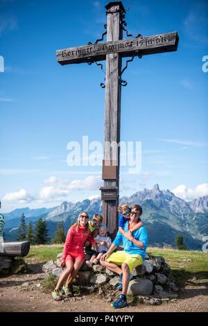 Österreich, Salzburg Land, Untertauern, Familie am Gipfelkreuz sitzen - Stockfoto