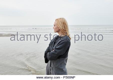 Niederlande, blonde junge Frau, die am Strand auf Distanz suchen - Stockfoto