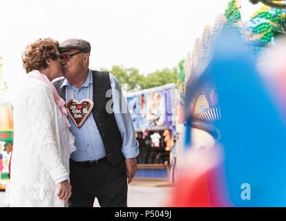 Senior Paar mit Lebkuchenherz küssen auf Messe - Stockfoto
