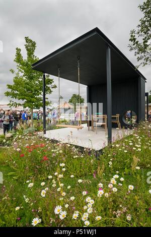 Menschen sehen gepflasterte Pavillon Sitzecke, Swing & bunten wildflowers - Ccla: eine Familie Garten, RHS Chatsworth Flower Show, Derbyshire, England, UK. - Stockfoto