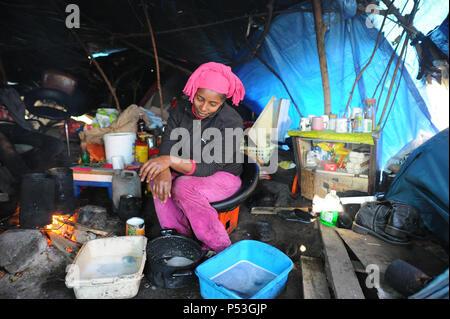 """Februar 19, 2015 - Calais, Frankreich: Portrait von Sally, eine illegale Migranten aus Erythrea versuchen, nach Großbritannien zu gelangen. Die 29-jährige Frau lebt seit fünf Monaten in diesem """"Dschungel"""" Camp mit ihrem Ehemann. Sie ist drei Monate schwanger. Sie ist unter der Plane, dass ihr Zelt- und Küchenbereich schützt fotografiert. Sie reiste durch Sudan, Libyen und Italien vor Calais. Hunderte von anderen illegalen Migranten leben in Zelten in einem Industriegebiet von Calais, wie sie für eine Gelegenheit, nach Großbritannien zu warten. Die Migranten, die meist aus Erythrea, Äthiopien, Afghanistan, Syrien, und - Stockfoto"""