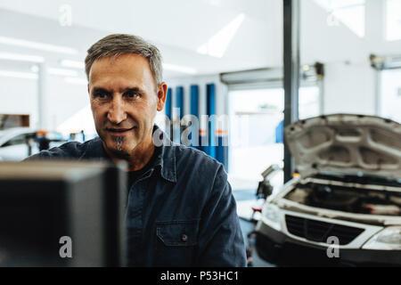 Reife männliche Mechaniker prüfen ein Auto mit Computer. Mechaniker das Auto die Diagnose auf dem Computer. - Stockfoto
