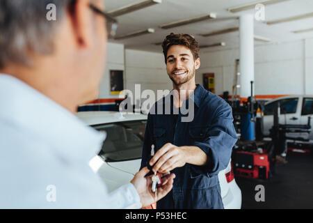 Automechaniker vorbeifahrenden Auto Schlüssel für die Autobesitzer, nachdem sein Fahrzeug reparieren. Mechaniker das Auto Schlüssel zum Kunden nach Wartungsarbeiten an der Garage. - Stockfoto