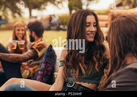 Glückliches Paar an einem Park mit Freunden auf der Rückseite sitzen. Männer und eine Frau auf einem Sommerfestival. - Stockfoto