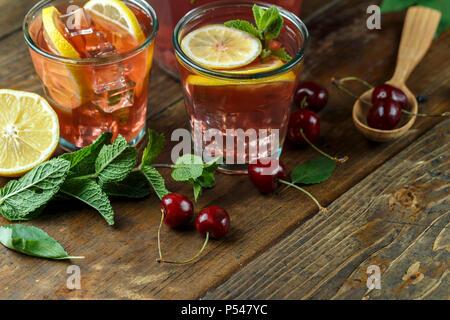 Hausgemachte Limonade mit Cherry, Minze und Zitrone in einem Glas Schale auf einem hölzernen Hintergrund. - Stockfoto