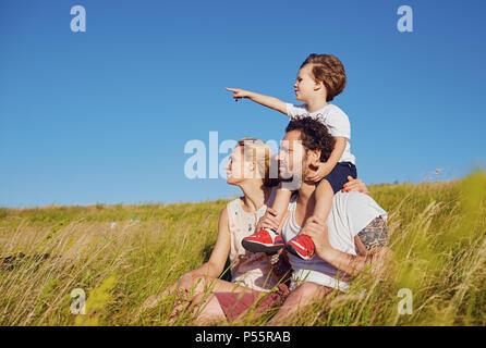 Glückliche Familie zusammen in der Natur gegen den blauen Himmel - Stockfoto