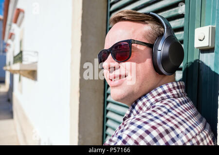Junger Mann genießen die Musik von schicken modernen Kopfhörer outdoor - Stockfoto