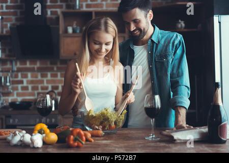 Schöne junge Paar vorbereiten, eine gesunde Mahlzeit zusammen, während freie Zeit zu Hause - Stockfoto