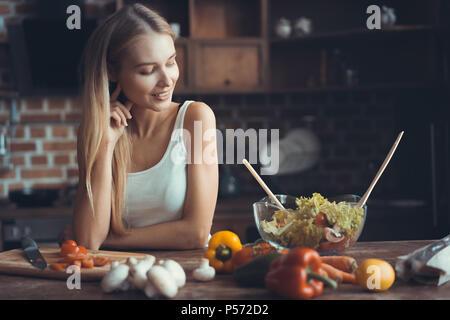 Junge Frau kochen. Gesunde Ernährung - Gemüsesalat. Ernährung. Diät-Konzept. Gesunde Lebensweise. Kochen zu Hause. Essen zubereiten - Stockfoto