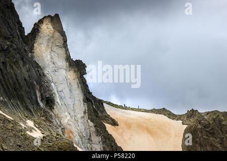 Zwei weit entfernte Bergsteiger Wandern auf dem schmalen Riff gegenüber der dramatischen, vertikalen Klippe auf Rila Gebirge, auf der Strecke zu Mussala Gipfel - Stockfoto