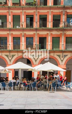 Cordoba cafe bar, Touristen in einem Café Terrasse im 17. Jahrhundert Plaza de la Corredera in Cordoba an einem Sommernachmittag, Andalusien, Spanien entspannen.