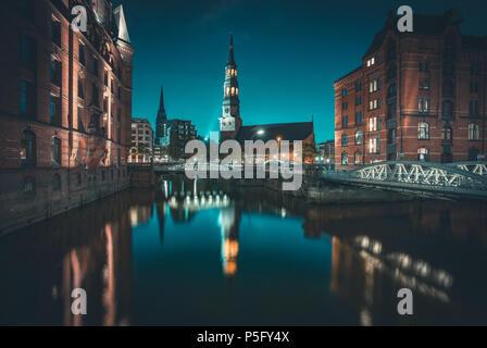 Klassische Ansicht der berühmten Speicherstadt mit St. Katharinen Kirche in schönen Post Sonnenuntergang Dämmerung Dämmerung, Hamburg beleuchtet, Ger - Stockfoto