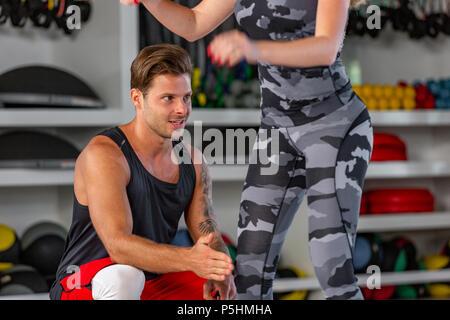 Tief in die Hocke. Fitness Paar in Sportswear tun Hocke Übungen im Fitnessstudio, - Stockfoto