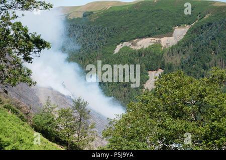 Aberystwyth Wales UK, 27. Juni 2018 Deutschland Wetter: ein Waldbrand, der gestern gestartet ist noch immer tobt, der die steilen Hänge des Rheidol Valley, einige Kilometer landeinwärts von Aberystwyth in Mid Wales. Das Gelände ist es für die Feuerwehr unmöglich - Mannschaften ihre Fahrzeuge zu erhalten, schließen Sie auf die Flammen, und das Feuer wird von einem Fachmann Hubschrauberbesatzung, die Fallen sind Tonnen von Wasser behandelt, geschöpft aus dem Fluss auf die brennenden Bäume. Photo Credit: Keith Morris/Alamy leben Nachrichten - Stockfoto
