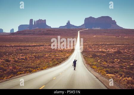 Classic panorama Blick auf junge Person zu Fuß auf den berühmten Forrest Gump highway im Monument Valley am Mittag, Arizona, USA - Stockfoto