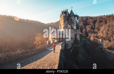 Wanderer auf dem Weg zum berühmten Burg Eltz beleuchtet im schönen Morgen bei Sonnenaufgang mit Lens Flare, Rheinland-Pfalz, Deutschland - Stockfoto