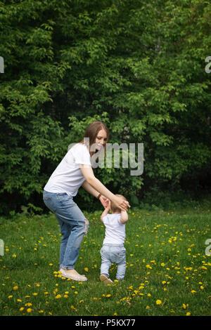Familie. Mutter und Sohn gehen herum Wiese halten sich an den Händen. Schwangere Mädchen hilft kleinen Jungen laufen lernen. - Stockfoto