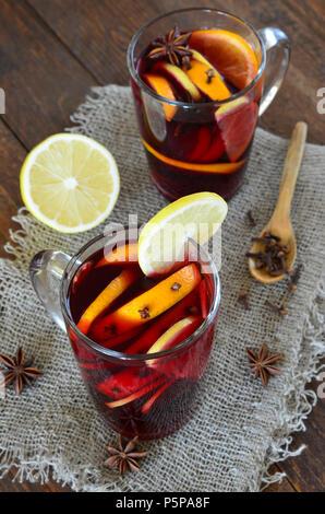 Glühwein mit Orangen- und Zitronenschale auf hölzernen Hintergrund - Stockfoto