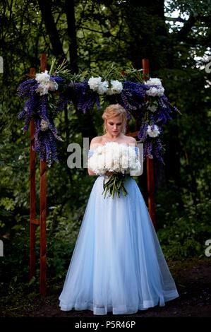Die Braut steht bei den Bogen, mit Blumen geschmückt, mit einem großen Blumenstrauß aus den weißen Pfingstrosen. Registrierung vor Ort im Park Hochzeit gehen und Foto s - Stockfoto