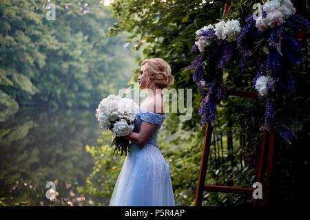 Die Braut steht bei den Bogen, mit Blumen geschmückt, mit einem großen Blumenstrauß aus den weißen Pfingstrosen. Registrierung vor Ort im Park Hochzeit gehen und Foto sh - Stockfoto