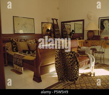 Faux leopard Haut werfen auf Stuhl unten Sleigh Bett mit Tier-print Kissen in der Portugiesischen Schlafzimmer - Stockfoto
