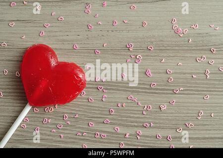 Ein rotes Herz Form Lutscher gegen einen hölzernen Hintergrund mit kleinen rosa Herzen isoliert - Stockfoto