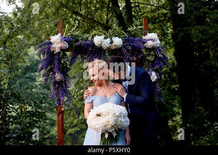 Die Braut und der Bräutigam stand auf der Arch, mit Blumen geschmückt, mit einem großen Blumenstrauß aus den weißen Pfingstrosen. Registrierung vor Ort im Park Hochzeit gehen ein - Stockfoto