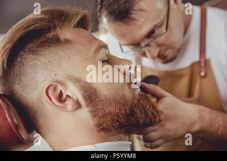 Mann in den Prozess der Trimmen ein Bart in einem Friseursalon. Foto im Vintage Style - Stockfoto