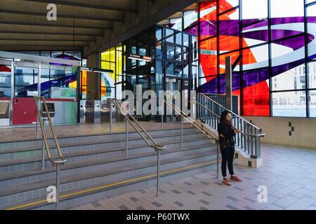 Junge Frau consulting Ihr Handy in Champ-de-Mars Metro Station, Montreal, Provinz Quebec, Kanada. - Stockfoto