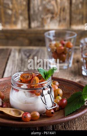 Käsekuchen creme Parfaits mit Stachelbeeren in den jar, köstliche Sommer keine-backen Dessert auf rustikalen Holztisch bereit zu essen - Stockfoto