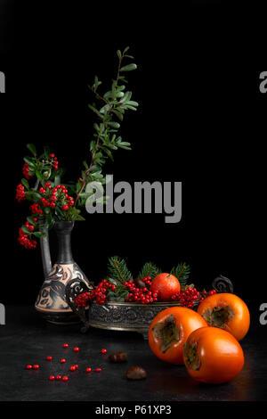 Stilleben mit Früchte fallen als kakipflaume, Kastanien und Mandarin orange, mit roten Beeren dekoriert. - Stockfoto