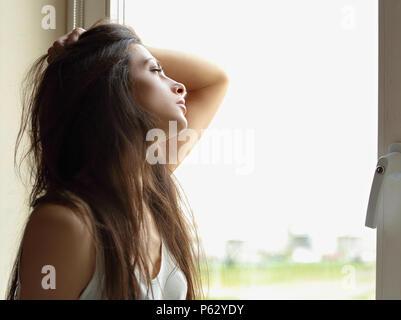 Schöne traurige einsame Frau denken und suchen Wenn das Fenster. Closeup Portrait - Stockfoto