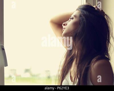 Schöne traurige einsame Frau denken und suchen Wenn das Fenster. Closeup getönten Portrait - Stockfoto