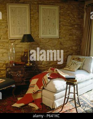Rot + Creme Gesteppte Patchwork Werfen Auf Weiß Liege Gegen Stein Wand Im  Wohnzimmer   Stockfoto