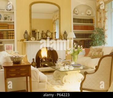 Große goldgerahmte Spiegel über Kamin mit brennenden Feuer im Wohnzimmer mit Erker Regale und Glas + stone Couchtisch - Stockfoto
