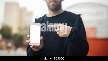 Der bärtige Mann hält das Telefon mit der rechten Hand und zeigt auf dem Bildschirm des mobilen. - Stockfoto