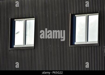 Zwei Fenster auf dunklen Außenwand aus Wellblech. - Stockfoto