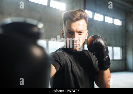 Thai Boxer in schwarzen T-Shirt gekleidet und Boxhandschuhen auf die Hände am Standort Leer - Stockfoto