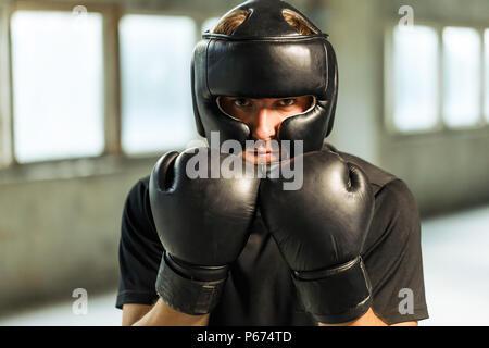Portrait Boxer in schwarzen T-Shirt, Maske gekleidet und Boxhandschuhen auf die Hände am Standort Leer - Stockfoto