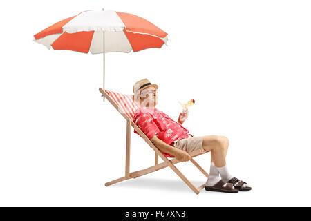 Ältere Touristen mit einem Cocktail und sitzen in einem Liegestuhl mit Sonnenschirm auf weißem Hintergrund - Stockfoto