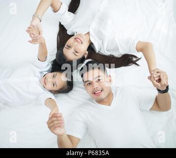Junge Familien mit Kindern auf dem Bett - Stockfoto