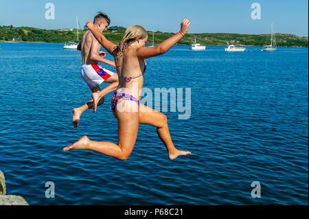 Schull, West Cork, Irland. 28 Juni, 2018. Ein junger Mann und eine Frau, die sich durch einen Sprung in das Wasser in Schull. Die Temperaturen bleiben in den hohen 20's Celsius morgen aber Regen ist über das Wochenende prognostiziert. Credit: Andy Gibson/Alamy Leben Nachrichten. - Stockfoto